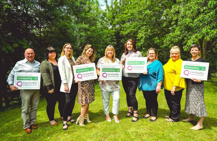 Photo of Home Instead Swindon team with CQC Outstanding signs