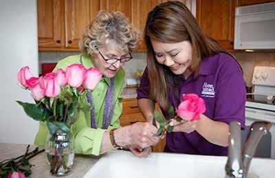 Client and CAREGiver with Flowers in the Kitchen