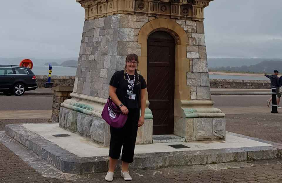Home Instead CAREGiver Megan Sharland standing in front of the clock tower on Exmouth seafront