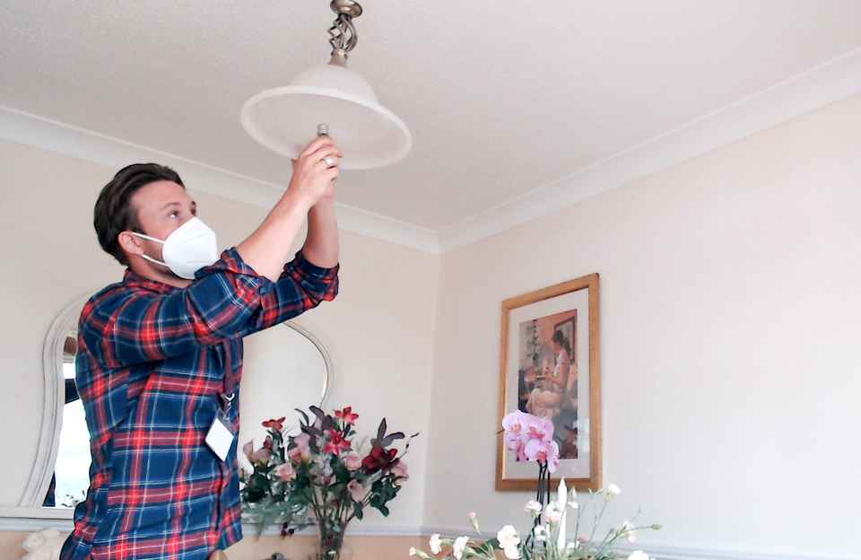 Caregiver changing lightbulb in client's home